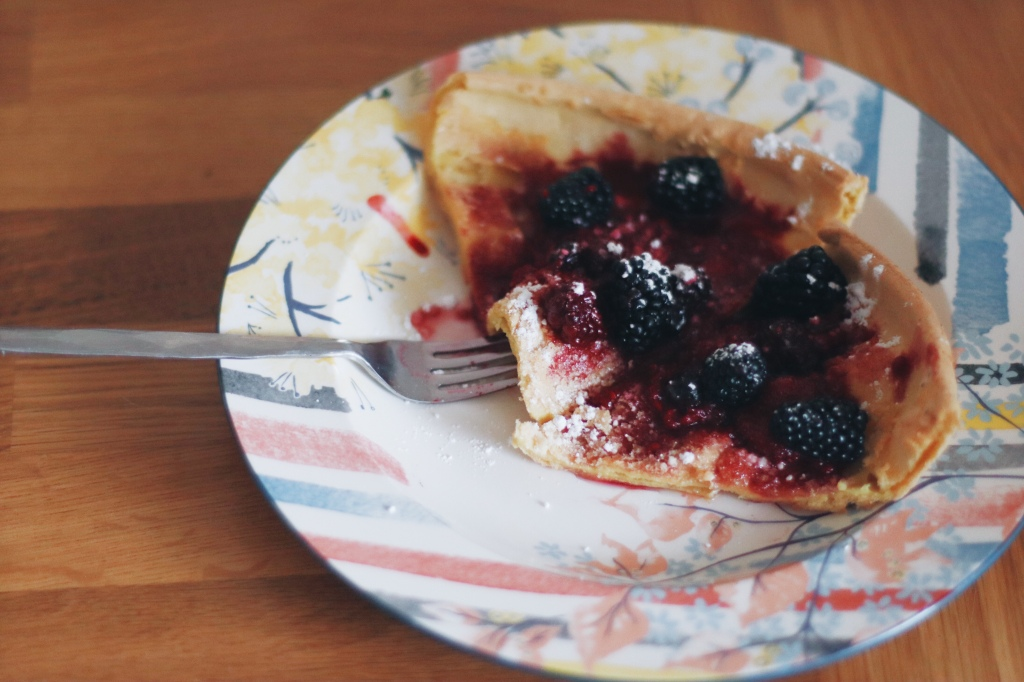 Dutch Baby Pancakes with berry compote, powdered sugar, and maple syrup